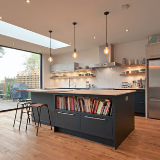 Photo of a medium sized contemporary single-wall open plan kitchen in Essex with a submerged sink, flat-panel cabinets, blue cabinets, white splashback, porcelain splashback, stainless steel appliances, medium hardwood flooring, an island and brown floors.