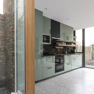 Idee per una cucina contemporanea di medie dimensioni con lavello da incasso, ante lisce, ante verdi, top in superficie solida, paraspruzzi nero, paraspruzzi con piastrelle in ceramica, elettrodomestici in acciaio inossidabile, pavimento alla veneziana, pavimento grigio e top nero