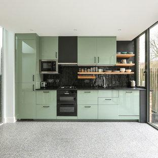 Inspiration för mellanstora moderna linjära svart kök, med en nedsänkt diskho, släta luckor, gröna skåp, bänkskiva i koppar, svart stänkskydd, stänkskydd i keramik, rostfria vitvaror, terrazzogolv och grått golv