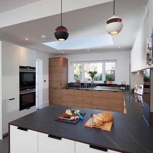ロンドンの中サイズのヴィクトリアン調のおしゃれなキッチン (ドロップインシンク、フラットパネル扉のキャビネット、中間色木目調キャビネット、パネルと同色の調理設備、セラミックタイルの床、グレーの床、黒いキッチンカウンター) の写真