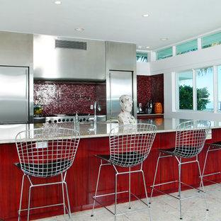 マイアミのコンテンポラリースタイルのおしゃれなII型キッチン (フラットパネル扉のキャビネット、ステンレスキャビネット、赤いキッチンパネル、モザイクタイルのキッチンパネル、シルバーの調理設備の) の写真
