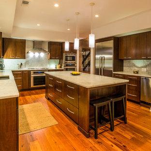 Foto di una cucina ad U design con ante lisce, ante in legno bruno, top in marmo, paraspruzzi in lastra di pietra, elettrodomestici in acciaio inossidabile, paraspruzzi bianco e lavello a doppia vasca
