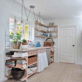 Создайте стильный интерьер: параллельная кухня-гостиная среднего размера в скандинавском стиле с накладной раковиной, открытыми фасадами, светлыми деревянными фасадами, белым фартуком, столешницей из дерева, деревянным полом и островом - последний тренд