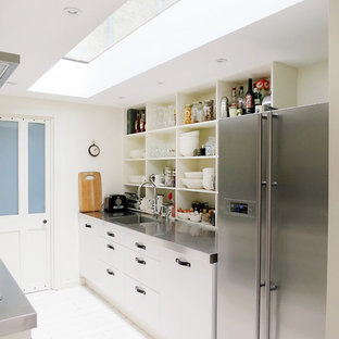 Eclectic kitchen in London with an integrated sink, open cabinets, white cabinets and stainless steel benchtops.