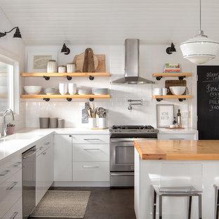 Cette image montre une cuisine rustique en L avec un évier intégré, un placard à porte plane, des portes de placard blanches, un plan de travail en bois, une crédence blanche, une crédence en carrelage métro, un électroménager en acier inoxydable et un îlot central.