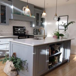 Design ideas for a medium sized contemporary u-shaped kitchen/diner in Surrey with a submerged sink, shaker cabinets, grey cabinets, granite worktops, white splashback, ceramic splashback, black appliances, light hardwood flooring, an island and brown floors.