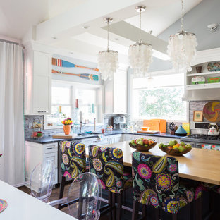 Eclectic kitchen ideas - Example of an eclectic l-shaped kitchen design in Kansas City with stainless steel appliances and an island