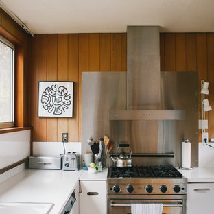 Photo of a small midcentury galley eat-in kitchen in Seattle with a double-bowl sink, flat-panel cabinets, white cabinets, laminate benchtops, metallic splashback, metal splashback and no island.