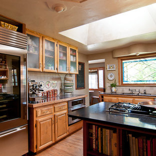 Inspiration for a timeless kitchen remodel in Portland with glass-front cabinets, light wood cabinets, beige backsplash and stainless steel appliances