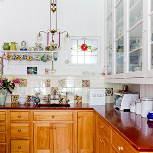 Ornate kitchen photo in Boston with glass-front cabinets, white cabinets, wood countertops and multicolored backsplash