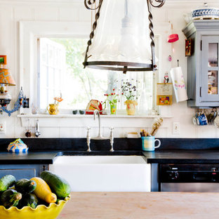 Example of a cottage kitchen design in New York with a farmhouse sink and wood countertops