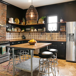 Eclectic kitchen remodeling - Example of an eclectic l-shaped brown floor kitchen design in Nashville with a drop-in sink, recessed-panel cabinets, black cabinets, wood countertops, beige backsplash, stainless steel appliances, an island and brown countertops