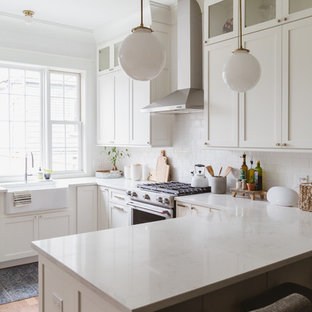 Beach style kitchen photos - Kitchen - beach style u-shaped kitchen idea in Chicago with a farmhouse sink, shaker cabinets, white cabinets, white backsplash, subway tile backsplash, stainless steel appliances, a peninsula and white countertops