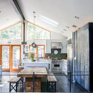 ロサンゼルスのインダストリアルスタイルのおしゃれなキッチン (アンダーカウンターシンク、落し込みパネル扉のキャビネット、白いキャビネット、緑のキッチンパネル、シルバーの調理設備の、塗装フローリング、黒い床、白いキッチンカウンター) の写真