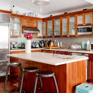Idéer för eklektiska kök, med luckor med glaspanel, skåp i mellenmörkt trä och stänkskydd med metallisk yta