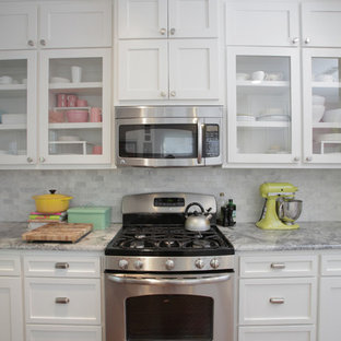 This is an example of an eclectic kitchen in Dallas with granite benchtops, shaker cabinets, white cabinets, white splashback, stone tile splashback and stainless steel appliances.