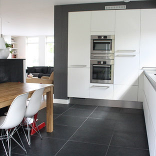 Contemporary kitchen pictures - Trendy l-shaped gray floor kitchen photo in Amsterdam with stainless steel appliances, flat-panel cabinets and white cabinets