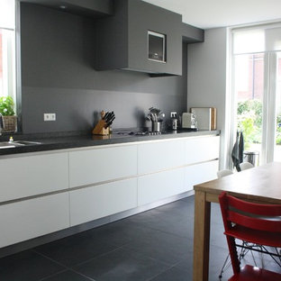 Contemporary kitchen inspiration - Example of a trendy kitchen design in Amsterdam with flat-panel cabinets, white cabinets and gray backsplash