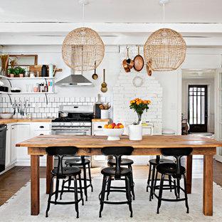 Immagine di una cucina shabby-chic style con lavello stile country, ante con riquadro incassato, ante bianche, top in legno, paraspruzzi bianco, elettrodomestici in acciaio inossidabile e parquet scuro
