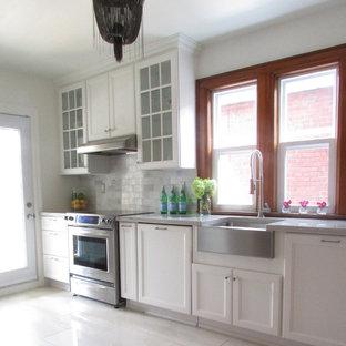 Пример оригинального дизайна интерьера: кухня в классическом стиле с раковиной в стиле кантри, фасадами с утопленной филенкой, белыми фасадами, техникой из нержавеющей стали и белым полом