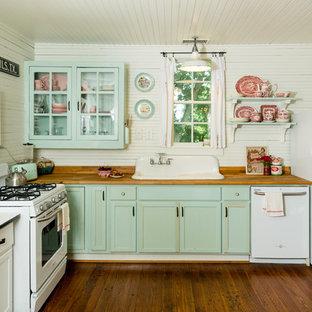 オースティンのシャビーシック調のおしゃれなL型キッチン (ドロップインシンク、落し込みパネル扉のキャビネット、緑のキャビネット、木材カウンター、白いキッチンパネル、木材のキッチンパネル、白い調理設備、無垢フローリング、茶色い床、茶色いキッチンカウンター) の写真