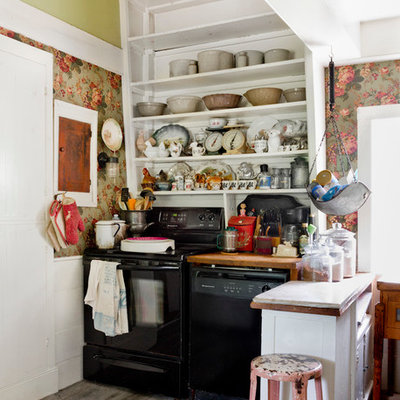 Kitchen - small shabby-chic style dark wood floor kitchen idea in New York with open cabinets, white cabinets, wood countertops, black appliances and a peninsula