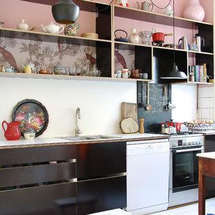 Minimalistisk inredning av ett kök, med öppna hyllor, svarta skåp, laminatbänkskiva, vita vitvaror och vitt stänkskydd
