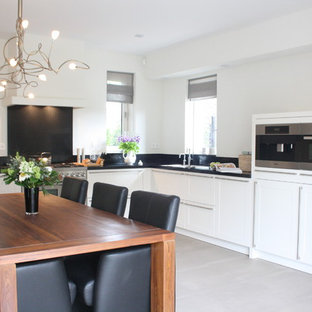Contemporary eat-in kitchen remodeling - Trendy l-shaped eat-in kitchen photo in Amsterdam with stainless steel appliances, flat-panel cabinets, white cabinets and black backsplash