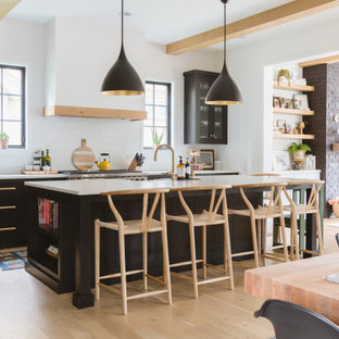 Scandinavian open concept kitchen ideas - Open concept kitchen - scandinavian light wood floor and exposed beam open concept kitchen idea in Chicago with glass-front cabinets, black cabinets, white backsplash, subway tile backsplash, an island and white countertops