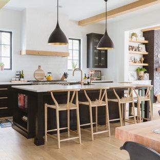 Foto de cocina nórdica, abierta, con armarios tipo vitrina, puertas de armario negras, salpicadero blanco, salpicadero de azulejos tipo metro, suelo de madera clara, una isla y encimeras blancas