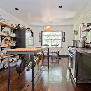This is an example of a traditional eat-in kitchen in Austin with stainless steel appliances, wood benchtops and open cabinets.