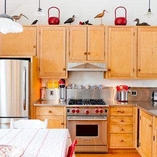 ニューヨークのエクレクティックスタイルのおしゃれなL型キッチン (ステンレスカウンター、ドロップインシンク、シェーカースタイル扉のキャビネット、淡色木目調キャビネット、メタリックのキッチンパネル、メタルタイルのキッチンパネル、シルバーの調理設備の、グレーのキッチンカウンター) の写真