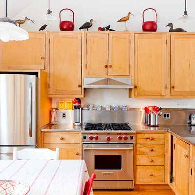 Eclectic l-shaped kitchen photo in New York with stainless steel countertops, a drop-in sink, shaker cabinets, light wood cabinets, metallic backsplash, metal backsplash, stainless steel appliances and gray countertops