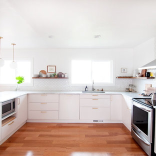 Mid-sized midcentury u-shaped kitchen in Denver with flat-panel cabinets, white cabinets, marble benchtops, white splashback, porcelain splashback, stainless steel appliances, a peninsula, an undermount sink and medium hardwood floors.