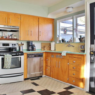 Inspiration for an eclectic u-shaped enclosed kitchen remodel in Portland with flat-panel cabinets, medium tone wood cabinets, tile countertops, yellow backsplash, ceramic backsplash, stainless steel appliances and green countertops