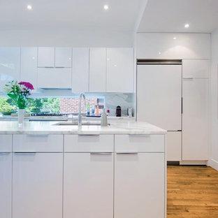 トロントの大きいコンテンポラリースタイルのおしゃれなキッチン (フラットパネル扉のキャビネット、白いキャビネット、大理石カウンター、白いキッチンパネル、白い調理設備、無垢フローリング、ダブルシンク、ガラスまたは窓のキッチンパネル) の写真