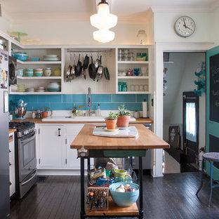 Ejemplo de cocina comedor en L, bohemia, de tamaño medio, con armarios abiertos, puertas de armario blancas, encimera de madera, salpicadero azul, salpicadero de azulejos de cerámica, electrodomésticos de acero inoxidable, suelo de madera oscura, una isla y fregadero encastrado