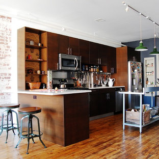 Inspiration for an industrial kitchen remodel in New York with flat-panel cabinets, dark wood cabinets and stainless steel appliances