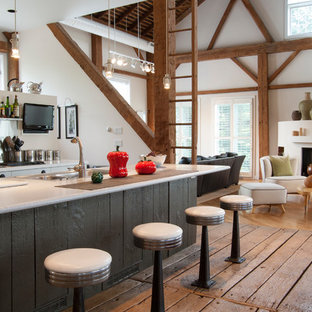 Example of a huge farmhouse galley medium tone wood floor open concept kitchen design in Cleveland with metallic backsplash, metal backsplash, an island, a double-bowl sink, flat-panel cabinets, white cabinets, solid surface countertops and stainless steel appliances