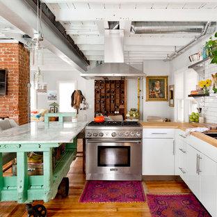 Создайте стильный интерьер: угловая кухня-гостиная в стиле фьюжн с тройной раковиной, плоскими фасадами, белыми фасадами, столешницей из дерева, белым фартуком, фартуком из плитки кабанчик, техникой из нержавеющей стали, паркетным полом среднего тона и островом - последний тренд