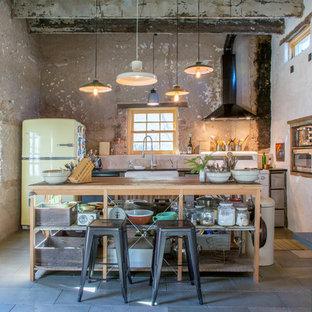 他の地域のエクレクティックスタイルのおしゃれなキッチン (エプロンフロントシンク、カラー調理設備、黒い床) の写真