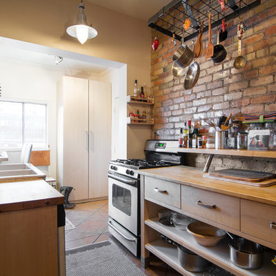 Enclosed kitchen - eclectic galley enclosed kitchen idea in Salt Lake City with a double-bowl sink, open cabinets, medium tone wood cabinets, wood countertops, mosaic tile backsplash and stainless steel appliances