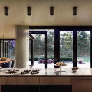 Inredning av ett modernt svart svart kök, med en undermonterad diskho, släta luckor, skåp i mellenmörkt trä, bänkskiva i kalksten, svart stänkskydd, stänkskydd i kalk, integrerade vitvaror, terrazzogolv, en köksö och grått golv