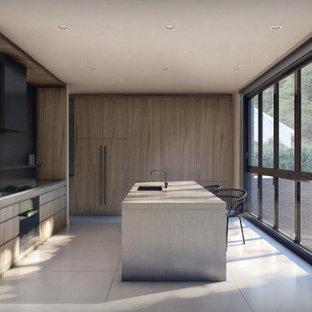 Modelo de cocina de galera, moderna, abierta, con fregadero bajoencimera, armarios con paneles lisos, puertas de armario de madera oscura, encimera de granito, salpicadero negro, electrodomésticos con paneles, suelo de baldosas de porcelana, una isla, suelo gris y encimeras grises