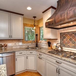 Klassische Wohnküche in L-Form mit Granit-Arbeitsplatte, Doppelwaschbecken, weißen Schränken, Küchengeräten aus Edelstahl, Kassettenfronten und Rückwand aus Schiefer in Sonstige