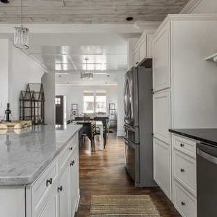 Inspiration for a small transitional l-shaped eat-in kitchen in Indianapolis with an undermount sink, recessed-panel cabinets, white cabinets, granite benchtops, black splashback, slate splashback, stainless steel appliances, medium hardwood floors, with island, brown floor and black benchtop.