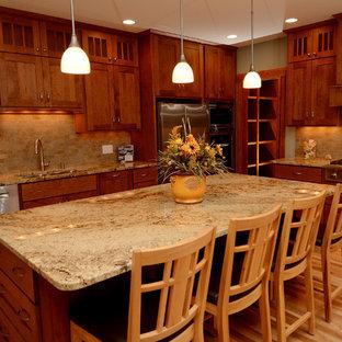 他の地域の中サイズのトランジショナルスタイルのおしゃれなキッチン (アンダーカウンターシンク、落し込みパネル扉のキャビネット、中間色木目調キャビネット、御影石カウンター、ベージュキッチンパネル、石タイルのキッチンパネル、シルバーの調理設備の、淡色無垢フローリング) の写真