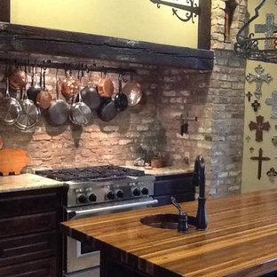 オクラホマシティのトランジショナルスタイルのおしゃれなアイランドキッチン (シングルシンク、木材カウンター、レンガのキッチンパネル、シルバーの調理設備、レイズドパネル扉のキャビネット、濃色木目調キャビネット、茶色いキッチンパネル、セメントタイルの床) の写真