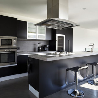 Design ideas for a large modern single-wall eat-in kitchen in Other with a drop-in sink, flat-panel cabinets, black cabinets, granite benchtops, black splashback, stainless steel appliances, with island, black floor, grey benchtop, slate splashback and ceramic floors.