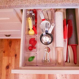 Imagen de cocina en U, clásica, grande, con armarios con paneles empotrados, puertas de armario blancas, encimera de granito, suelo de madera clara y una isla
